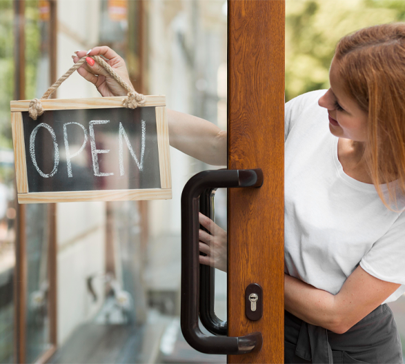 business owner holding an open sign