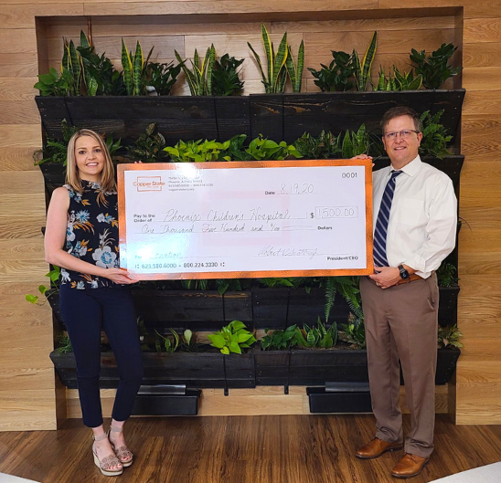 Copper State CEO and Branch Manager holding a check