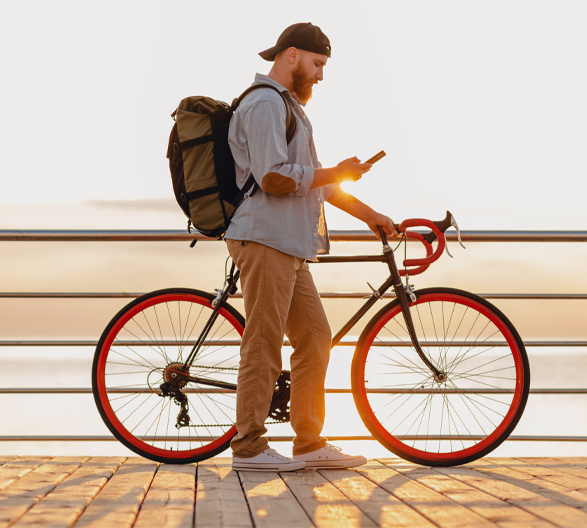 man on cell phone holding bike