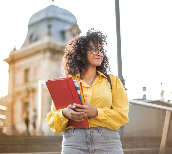Female college student holding books standing on stairs
