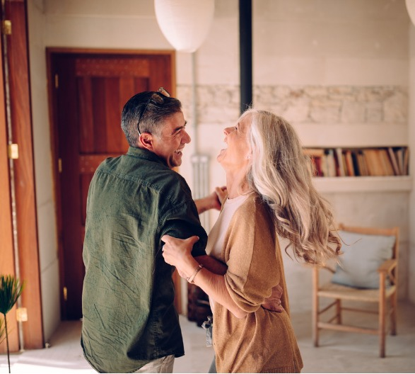 happy-senior-couple-dancing-and-laughing-together-at-home