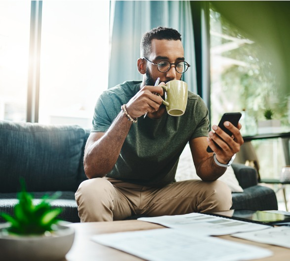 Man sitting on the couch looking at his phone and drinking coffee