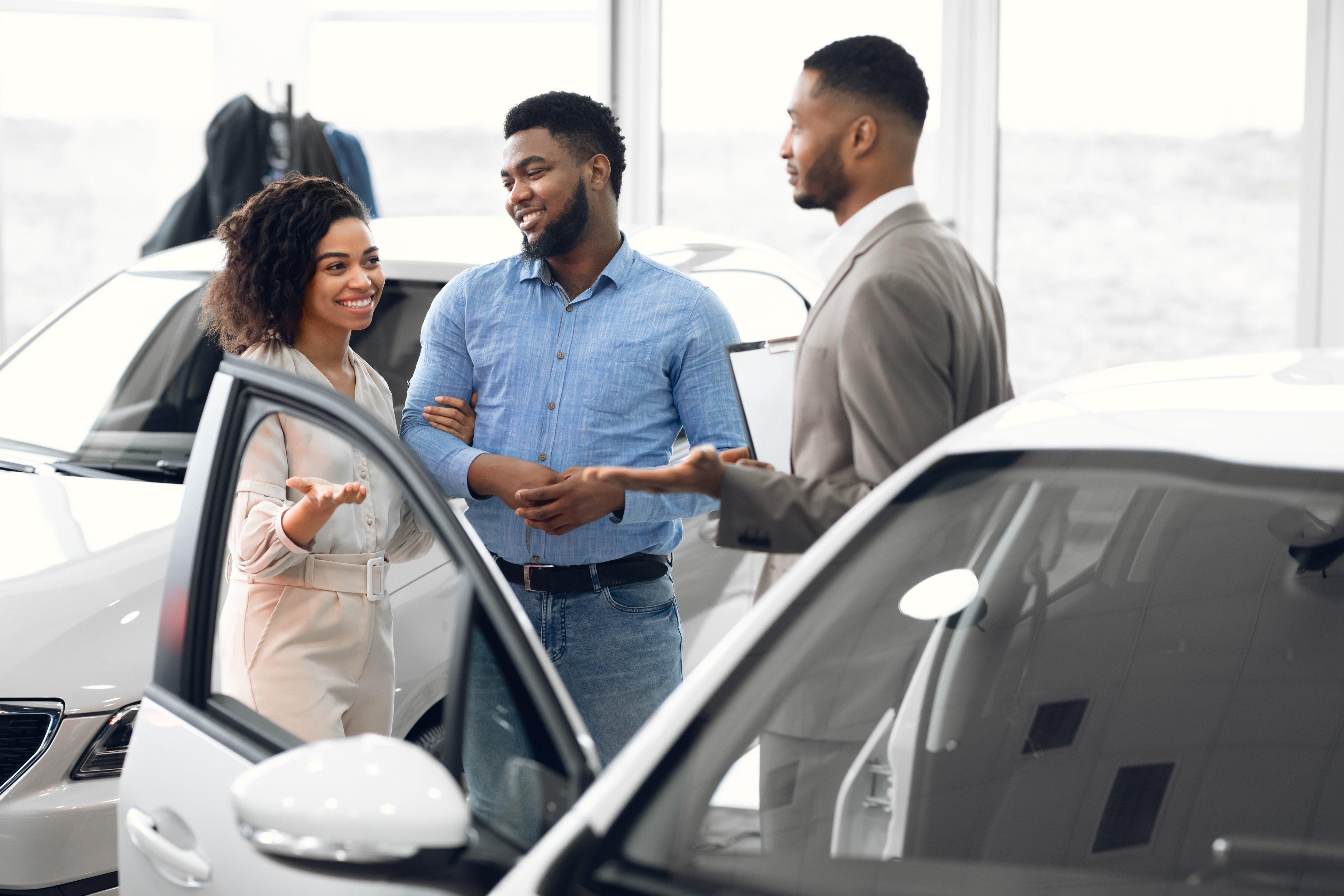 Man and woman talking to car salesman