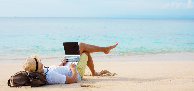 man-lying-on-beach-with-laptop
