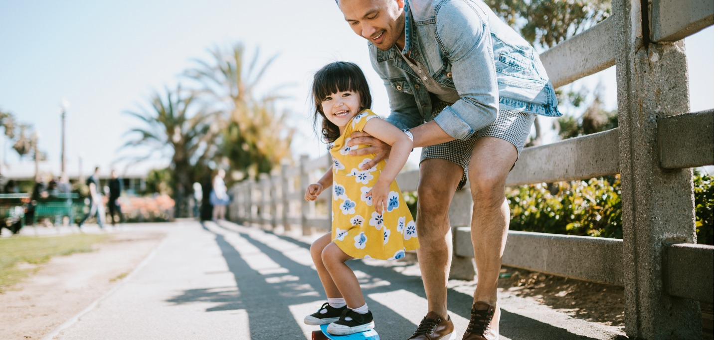 father-helps-young-daughter-ride-skateboard